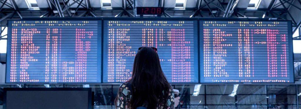 אישה מסתכלת על לוח טיסות בשדה התעופה